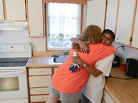 Day 3: Kathleen, House Captain, hugs one of the homeowners in her remodeled kitchen